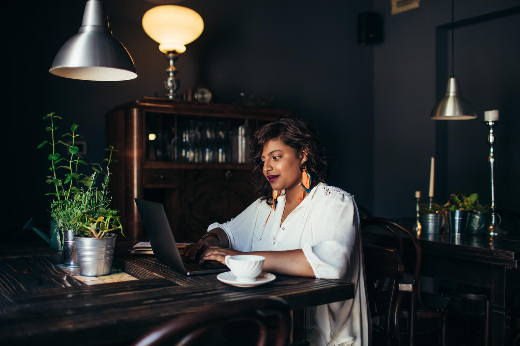 woman sitting alone at a table drinking coffee and working on a laptop