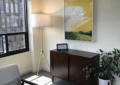 Our office chair in front of window with painting